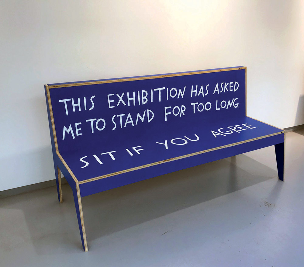 A blue bench with hand-painted white text reads: This exhibition has asked me to stand for too long. Sit if you agree.