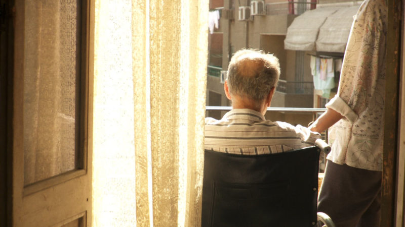 A seated man on a balcony with balding hair with his back turned against us, with a woman's hand on his shoulder. Bright sunlight is reflected off a curtain.