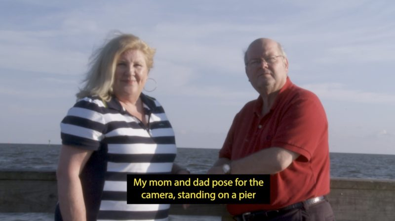 "A white woman with shoulder-length blonde hair stands next to a bald man wearing glasses, in front of an ocean and a cloudy blue sky. They both stare at the camera. A caption at the bottom of the image reads: ""My mom and dad pose for the camera, standing on a pier""."