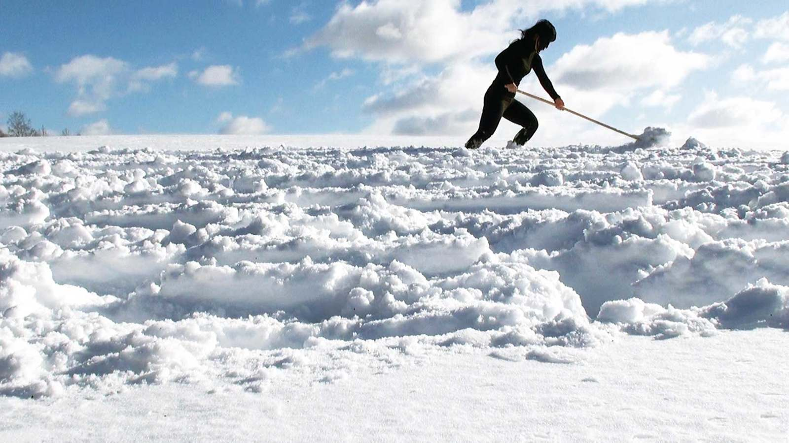 On a snowy field on a sunny day, a woman dressed in black is pushing snow with a broom.